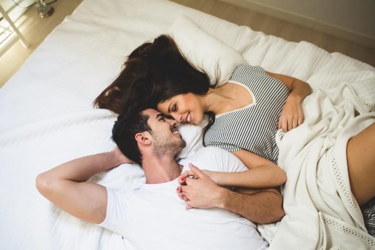 couple-couche-sur-le-lit-tenant-la-main-et-regardant-dans-les-yeux-les-uns-des-autres