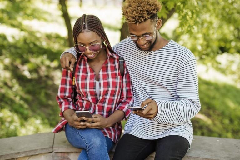 couple-noirs-avec-telephones-dans-le-parc