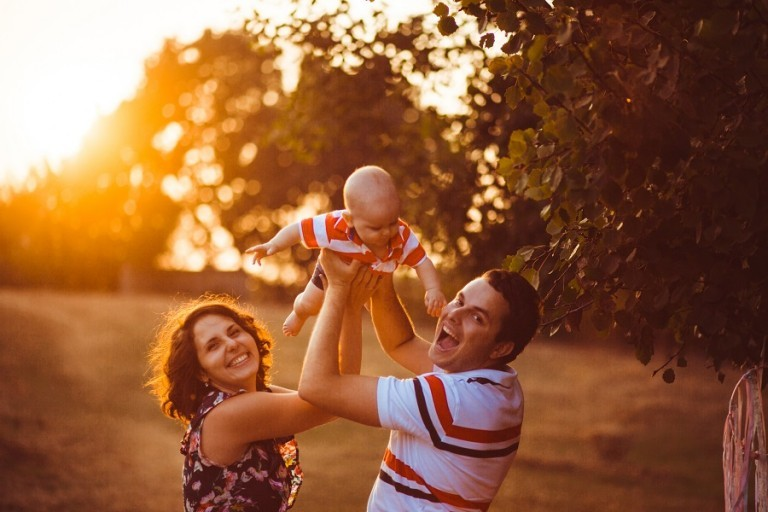 Cheerful parents hold their little son up standing outside in the evening