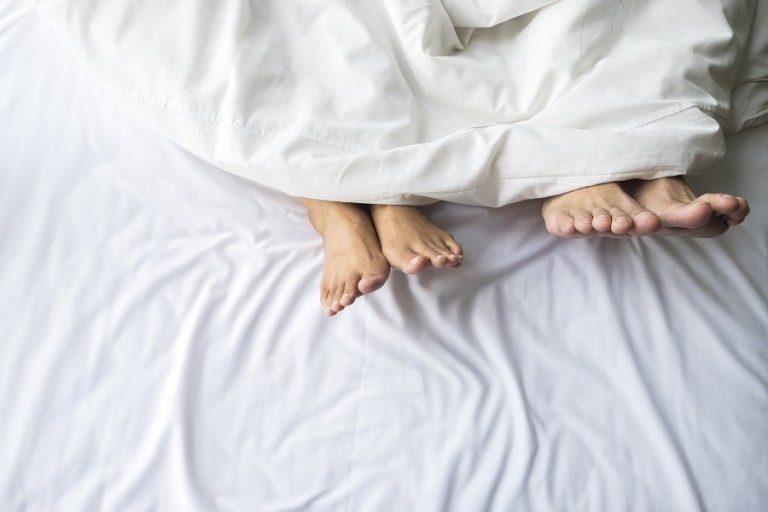 Feet of couple sleeping side by side in comfortable bed. Close up of feet in a bed under white blanket. Bare feet of a man and a woman peeking out from under the cover.Top view with background copy space.